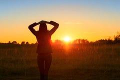 La muchacha en la puesta del sol del contraluz Imagen de archivo