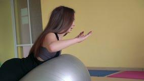 La muchacha en la ropa de deportes que hace ejercicios traseros de la desviación con el fitball 4k almacen de metraje de vídeo