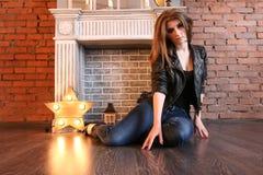 La muchacha en las chaquetas de cuero negras que plantean sentarse en el piso Imagenes de archivo