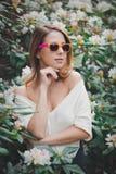 La muchacha en las gafas de sol blancas acerca a las flores Imágenes de archivo libres de regalías