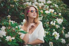 La muchacha en las gafas de sol blancas acerca a las flores Imagen de archivo libre de regalías