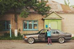La muchacha en los años noventa está sobre los coches imagenes de archivo