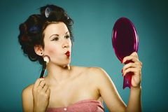 La muchacha en los bigudíes que diseñan la aplicación del pelo compone Foto de archivo libre de regalías