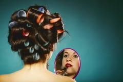 La muchacha en los bigudíes que diseñan la aplicación del pelo compone Fotografía de archivo libre de regalías