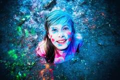 La muchacha en los colores de la sonrisa de Holi Imagen de archivo libre de regalías