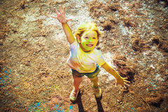 La muchacha en los colores de la sonrisa de Holi Foto de archivo libre de regalías