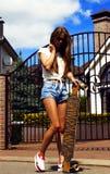 La muchacha en los pantalones cortos blancos del chaleco y de los vaqueros presenta con imagen de archivo