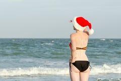 La muchacha en los sombreros de Papá Noel con el Año Nuevo de la inscripción en la parte posterior mira en la distancia Orilla de Imagenes de archivo