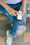 La muchacha en los vaqueros rasgados que se sientan en un banco y limpia el teléfono móvil Foto de archivo