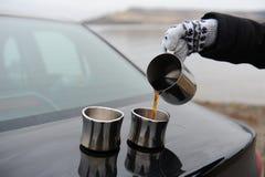 La muchacha en manoplas vierte el café de la jarra en las tazas en el tronco de coche Paisaje monocromático deshabitado Foto de archivo