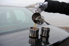 La muchacha en manoplas vierte el café de la jarra en las tazas en el tronco de coche Paisaje monocromático deshabitado Imagenes de archivo
