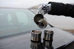 La muchacha en manoplas vierte el café de la jarra en las tazas en el tronco de coche Paisaje monocromático deshabitado Imagen de archivo libre de regalías