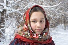 La muchacha en mantones rojos contra el contexto de un landscap del invierno Imágenes de archivo libres de regalías