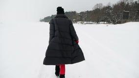 La muchacha en medias y botas rojas está en una bahía congelada almacen de video