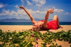 la muchacha en mentiras del rojo en la arena levanta las manos a un lado cerca de enredaderas Foto de archivo