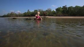 La muchacha en mentiras del traje de baño en el mar alisa juegos del guitarrista del pelo metrajes