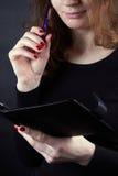 La muchacha en miradas sonrientes de un suéter negro en un cojín Fotografía de archivo