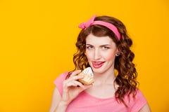 La muchacha en modelo-estilo rosado del vestido come la torta con crema Foto de archivo libre de regalías