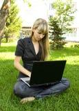La muchacha en negro, en el césped con una computadora portátil Fotografía de archivo