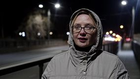 La muchacha en la noche va en el puente en la ciudad Front View La c?mara est? en el movimiento C?mara lenta Luces visibles de la metrajes