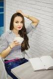La muchacha en paño casual puso la mano en la cabeza que se inclinaba en la pared de ladrillo Foto de archivo libre de regalías