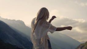 La muchacha en pantalones cortos elegantes de los vaqueros se está colocando en el top de la montaña, moviéndose hacia el sol