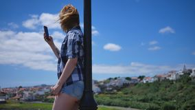 La muchacha en pantalones cortos cortos se coloca en el muelle con el teléfono almacen de video