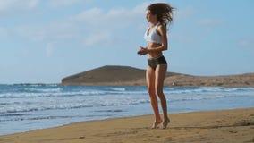 La muchacha en pantalones cortos y camiseta de la ropa de deportes realiza saltos con posiciones en cuclillas y aplaude en la pla metrajes