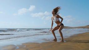 La muchacha en pantalones cortos y camiseta de la ropa de deportes realiza saltos con posiciones en cuclillas y aplaude en la pla almacen de metraje de vídeo