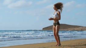 La muchacha en pantalones cortos y camiseta de la ropa de deportes realiza saltos con posiciones en cuclillas en la playa cerca d almacen de metraje de vídeo