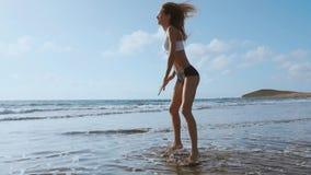 La muchacha en pantalones cortos y camiseta de la ropa de deportes realiza saltos con posiciones en cuclillas en la playa cerca d metrajes