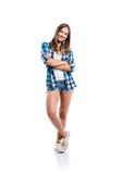La muchacha en pantalones cortos y la camisa comprobada, brazos cruzaron, aislado Imagen de archivo libre de regalías