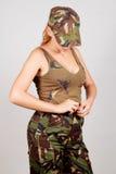 La muchacha en pantalones desabrochados ropa militar Fondo gris imagenes de archivo