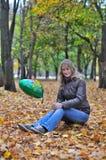 La muchacha en parque del otoño con el globo se sienta en el tocón Foto de archivo libre de regalías