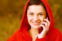 La muchacha en parque habla por el teléfono Foto de archivo
