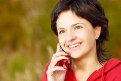 La muchacha en parque habla por el teléfono Imagen de archivo