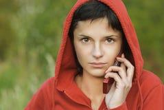 La muchacha en parque habla por el teléfono Imágenes de archivo libres de regalías