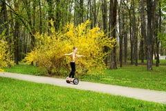 La muchacha en paseos de una chaqueta del oro gira en un hoverboard sobre las trayectorias del parque imagen de archivo