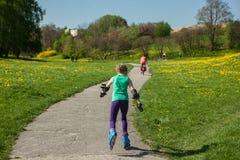 La muchacha en patines en línea aprende montar Fotos de archivo
