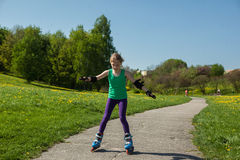 La muchacha en patines en línea aprende montar Fotografía de archivo