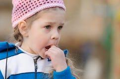 La muchacha en pensamiento pegó un finger su boca Fotos de archivo libres de regalías