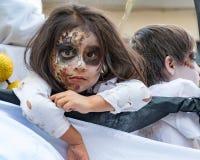 La muchacha en pintura de la cara mira fijamente fuera del flotador en desfile en Cuenca, Ecua Foto de archivo