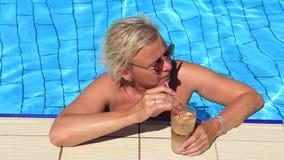 La muchacha en la piscina que bebe un cóctel almacen de video