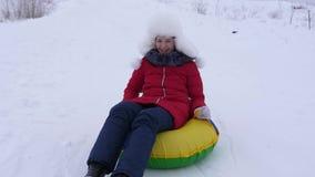 La muchacha en la placa nevosa rueda abajo de la alta montaña nevosa y de risas con placer El adolescente juega en invierno con l almacen de metraje de vídeo