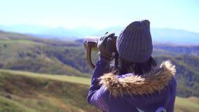 La muchacha en la plataforma de observación mira las montañas a través de los prismáticos y después mira en la cámara almacen de video