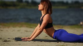 La muchacha en la playa ejercita actitud de la cobra de la yoga Primer horizontal del cableado almacen de metraje de vídeo