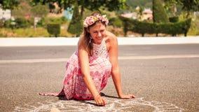 La muchacha en posiciones en cuclillas de la guirnalda dibuja con tiza en el pavimento del asfalto almacen de video