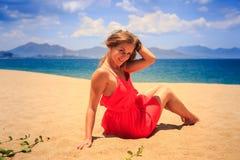 la muchacha en rojo se sienta en miradas del pelo de los tactos de la arena hacia abajo contra el mar Foto de archivo