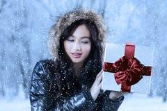 La muchacha en ropa caliente sostiene un regalo Foto de archivo libre de regalías