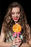 La muchacha en ropa colorida come la piruleta coloreada sabrosa imagen de archivo libre de regalías